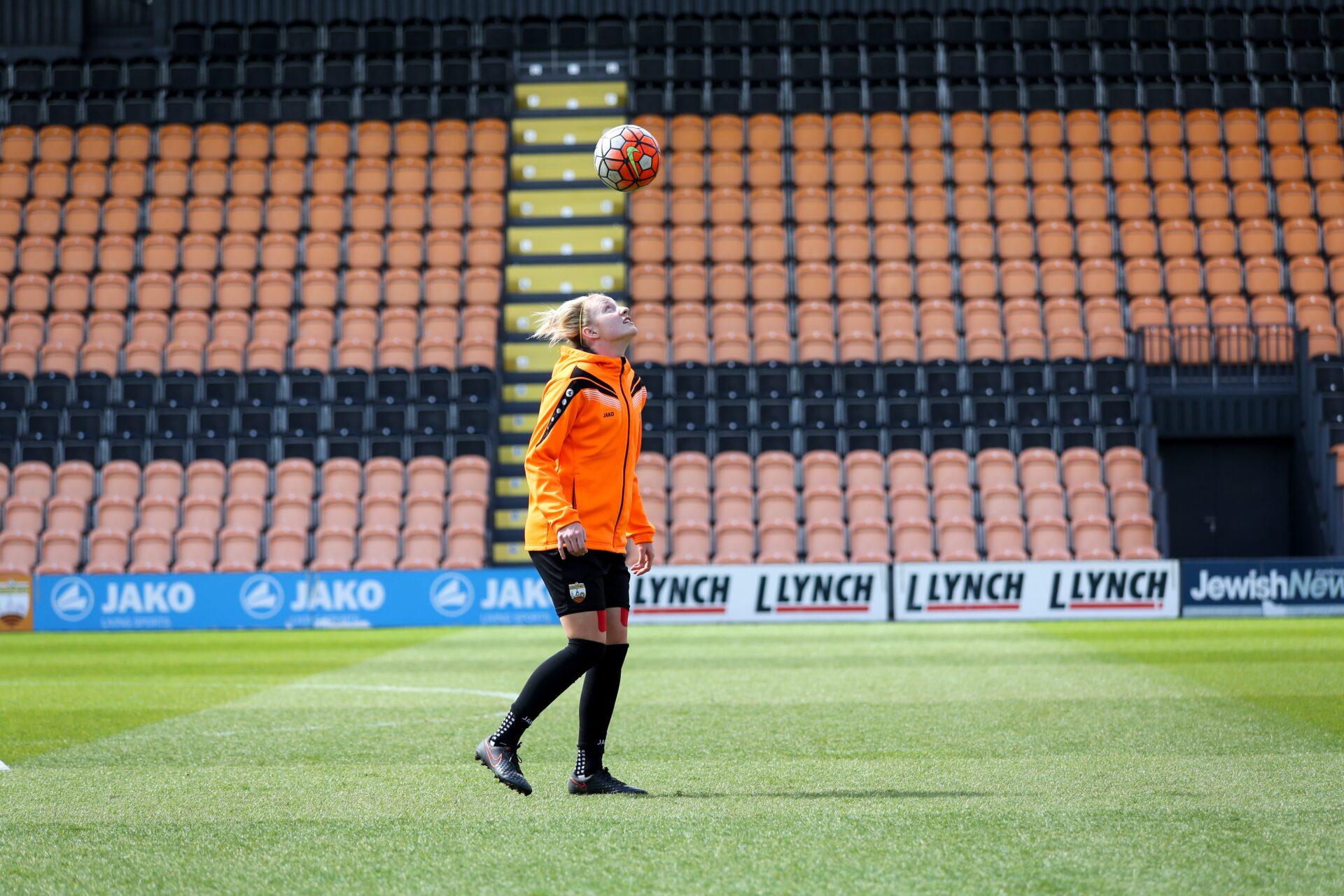 Jo Wilson heading a ball during warm-ups before a football match